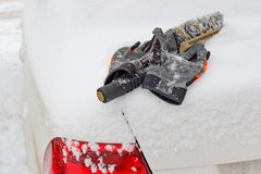 雪在一辆多雪的汽车的起动盒盖的刷子和冬天手套 免版税库存照片
