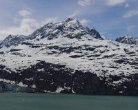 雪在冰河海湾的加盖的山 图库摄影