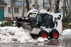 雪在城市的街道上的清洁机器 库存图片