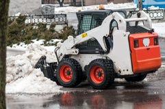 雪在城市的街道上的清洁机器 免版税图库摄影
