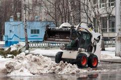 雪在城市的街道上的清洁机器 免版税库存图片