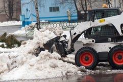 雪在城市的街道上的清洁机器 库存照片