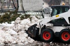 雪在城市的街道上的清洁机器 图库摄影