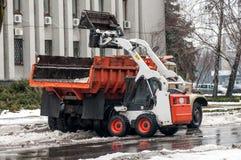 雪在城市的街道上的清洁机器 免版税库存照片