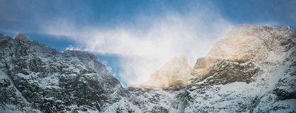雪在山峰的风暴和太阳射线 库存图片