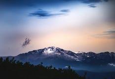 雪在日落或日出-矛峰顶的加盖的山 免版税库存照片