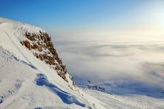 雪在有趣的纹理和冰柱结冰了在沿峭壁和大雾的岩石在一个冷的冬日 免版税库存照片