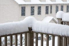 雪在阳台栏杆的被堆的上流  免版税库存图片