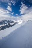 滑雪在Kitzbuehel滑雪胜地和享用阿尔卑斯的滑雪者观看fr 免版税库存图片