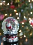 雪地球的滑冰的圣诞老人与树在背景中 库存图片