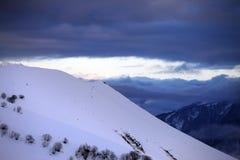 滑雪场地外的倾斜和多云天空在日落 免版税库存照片