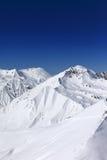 滑雪场地外的倾斜和蓝色清楚的天空在太阳天 免版税库存照片