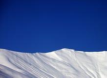 滑雪场地外的倾斜和蓝色清楚的天空在好冬日 免版税库存图片