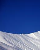 滑雪场地外的倾斜和蓝色清楚的天空在好冬日 免版税图库摄影