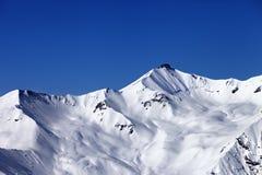 滑雪场地外的多雪的倾斜和蓝色清楚的天空 免版税库存图片
