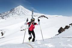 滑雪对山的登山家攀登与滑雪被束缚到在背景火山的背包 免版税库存照片