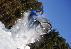 雪山骑自行车的人 免版税图库摄影