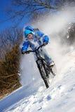 雪山骑自行车的人 免版税库存图片