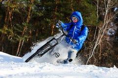 雪山骑自行车的人 免版税库存照片