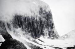 雪崩中断盖帽留下了山准备好的正确的树荫发光的倾斜雪山顶给顶层 免版税库存图片