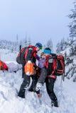 滑雪巡逻运载受伤的女子滑雪者担架 库存图片