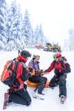 滑雪巡逻队抢救妇女被伤的胳膊 免版税图库摄影