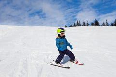 滑雪帽滑雪的男孩在下坡雪 库存照片