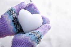 雪心脏在有手套的手上 图库摄影