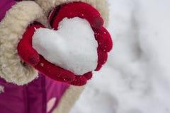 雪心脏在他的手上。 免版税库存照片