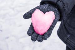 雪心脏在他的手上。 库存图片