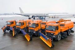 雪撤除机器在乘客飞机的背景中连续停放了在机场 免版税库存照片
