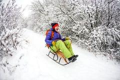 雪撬的一个女孩从山乘坐 免版税图库摄影