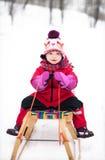 雪撬的小女孩 免版税库存照片