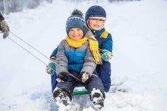 雪撬的愉快的男孩 演奏雪冬天的子项 免版税库存照片