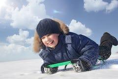 雪撬的愉快的男孩 免版税库存照片