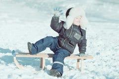 雪撬的男孩有接近的眼睛的享受冬天的 库存照片