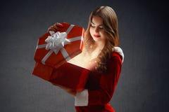 雪未婚一套红色衣服的美丽的女孩打开一件礼物新年2018,2019 免版税库存照片