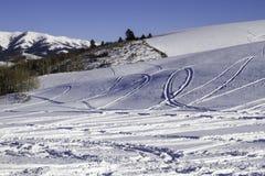 雪机器跟踪在雪的文字 免版税库存照片