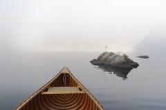 雪松独木舟和岩石在一个有薄雾的Ontario湖 库存照片