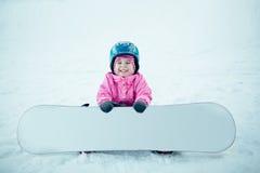 雪板冬季体育 使用与雪的小孩女孩佩带温暖的冬天穿衣 免版税库存图片
