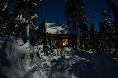 雪板和滑雪在房子瑞士山中的牧人小屋在冬天森林里有雪的在山 库存图片