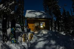 雪板和滑雪在房子瑞士山中的牧人小屋在冬天森林里有雪的在山 库存照片