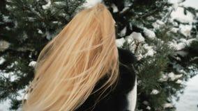 雪树的白肤金发的妇女高兴旋转并且送亲吻 影视素材