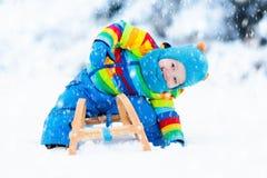 雪橇乘驾的男孩 儿童sledding 与爬犁的孩子 库存图片