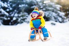 雪橇乘驾的男孩 儿童sledding 与爬犁的孩子 免版税库存图片