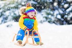雪橇乘驾的男孩 儿童sledding 与爬犁的孩子 免版税图库摄影