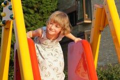 雪橇的逗人喜爱和愉快的小女孩在儿童操场 库存照片