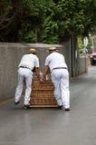 雪橇车手移动的传统藤茎爬犁下坡在丰沙尔街道上  Monte公园,马德拉岛 免版税库存图片