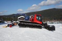 雪清洁推土机,清洗的滑雪倾斜,站立在晴朗的天气的山滑雪胜地 免版税库存图片