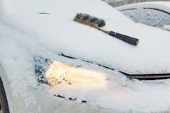 雪清洁的刷子在一辆积雪的汽车的敞篷 库存照片